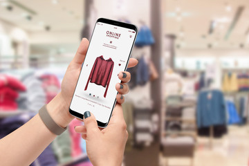 Female person shopping online with smartphone, clothing store in background