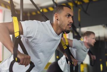Mężczyźni wykonujący trening TRX na siłowni