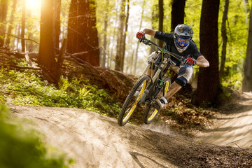 The cyclist on the downhill bike goes through the forest