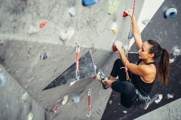 Beautiful young woman in black outfit climbing on practical wall in gym, bouldering, extreme sport, rock-climbing concept.