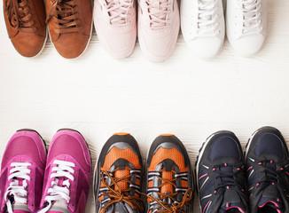 Trzy pary kolorowych butów do biegania / butów do ćwiczeń na podłodze w sklepie sportowym / obuwniczym. Potencjalne miejsce na podłodze.