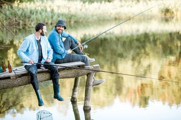 Dwaj męscy przyjaciele ubrani w niebieskie koszule łowią razem z siatką i wędką siedzącą na drewnianym molo podczas porannego światła na jeziorze