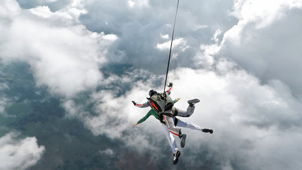 Skydiving tandem falling into the clouds