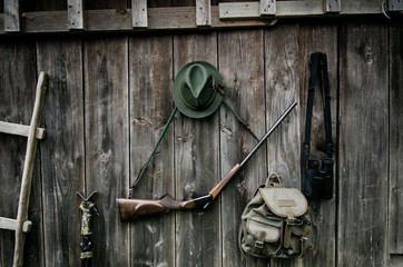 Professional hunters equipment for hunting. Rifle, hat, bag and others on a wooden black background.