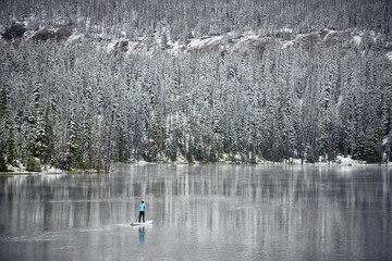 a woman paddle boarding on a mountain lake in the winter