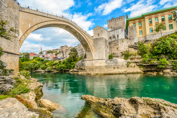 The emerald green waters of the river Neretva flow under the Mostar Bridge in the ancient city of Mostar, Bosnia and Herzegovina