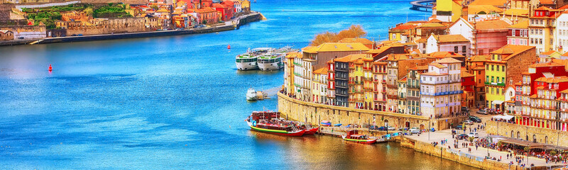 Porto, Portugal old town ribeira aerial promenade view with colorful houses, Douro river and boats, banner panoramic view