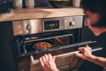 Woman checking apple pie in oven