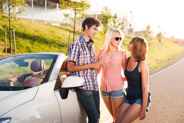 Drei junge Erwachsene stehen neben einem Cabrio