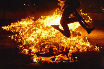 Summer solstice celebration in Spain. Woman jump. Fire flames