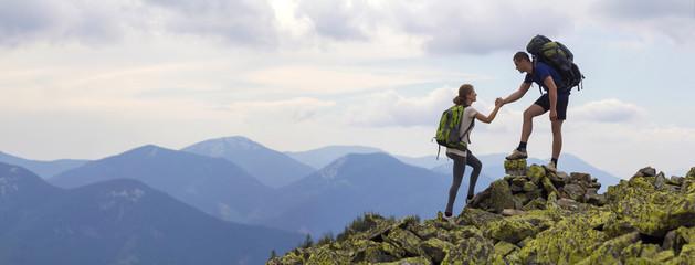 Młodzi turyści z plecakami, wysportowany chłopiec pomaga szczupłej dziewczynie wspinać się na skalisty szczyt na jasnym tle nieba i pasma górskiego. Pojęcie turystyki, podróży i zdrowego stylu życia.
