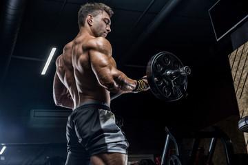 Młody brutalny sportowiec to kulturysta z doskonałym abs, ćwiczący na siłowni. Koncepcja - siła, kulturystyka, styrodes, podnoszenie ciężarów, dieta, mięśnie, odżywianie sportowe, osobisty trener