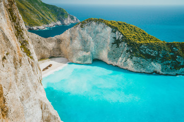 Famous shipwreck on Navagio beach with turquoise blue sea water surrounded by huge white cliffs. Famous landmark location on Zakynthos island, Greece