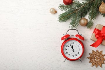 Flat lay composition with alarm clock and festive decor on wooden background. Christmas countdown