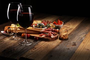 Zestaw włoskich przekąsek do antipasti. Odmiana sera, śródziemnomorskie oliwki, crudo, prosciutto di parma, salami i wino w kieliszkach na drewnianym tle grunge.