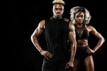 Fitness couple of athletes posing on black background, healthy lifestyle body care. Sport concept with copy space.