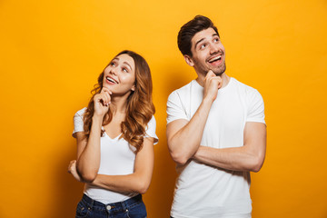 Image of cheerful young people man and woman in basic clothing laughing and touching chin while looking aside, isolated over yellow background