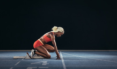 Woman sprinter using a starting block to start her sprint on a r