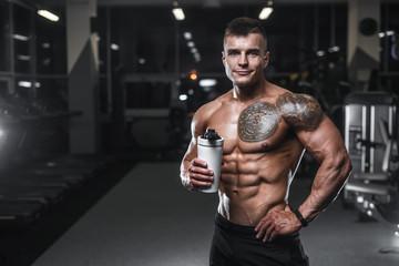 Przystojny silny kulturysta wysportowanych mężczyzn pompowania mięśni z hantlami