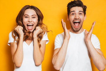 Photo of beautiful admired couple man and woman in basic clothing screaming in surprise or delight and touching cheeks, isolated over yellow background