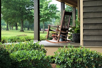 A wooden rocking chair on the beautiful terrace view is waiting for someone to relax on. Ga USA