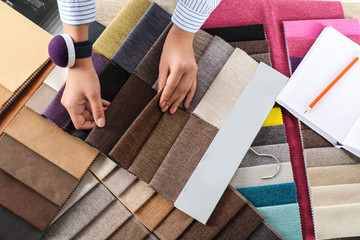 Young woman choosing among upholstery fabric samples, closeup. Interior design