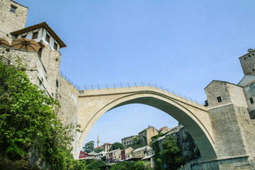 Old Bridge of Mostar during a sunny afternoon, with the old city visible in the background. This bridge is the symbol of the war torn main city of Herzegovina, in Bosnia..