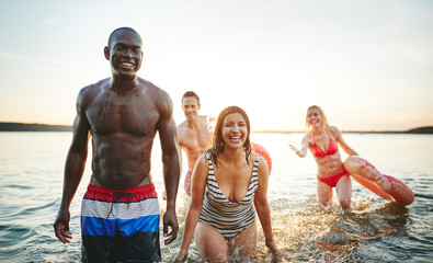 Laughing young friends wearing swimsuits splashing together in a