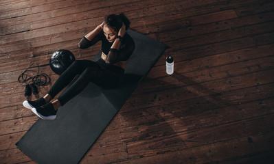 Kobieta robi brzuch ćwiczenia na siłowni