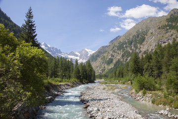 mountain stream in italian national park gran paradiso with snow capped mountains in the background