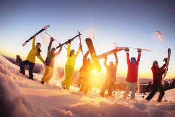 Happy friends at ski resort having fun sunset