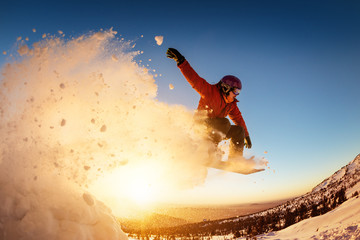 Snowboarder jumps sunset with snow dust