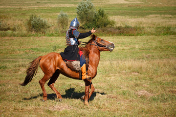 Summer. Reconstruction. Medieval armored knight on horse. Equestrian soldier in historical costume. Reenactor
