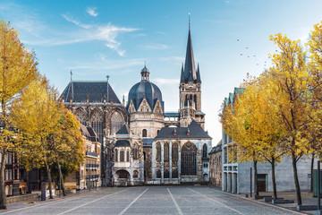 Niemiecka katedra w Aachen podczas spadku z żółtymi liśćmi przy drzewami z niebieskim niebem