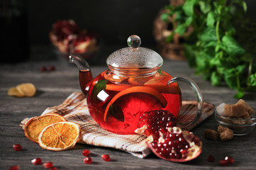 Pomegranate tea with orange on a wooden table in a rustic style