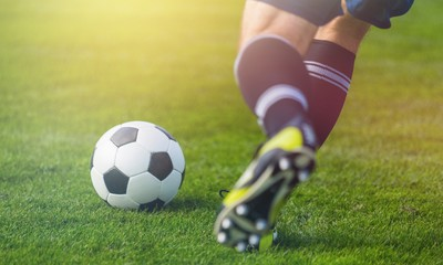 Działający gracz piłki nożnej na trawie
