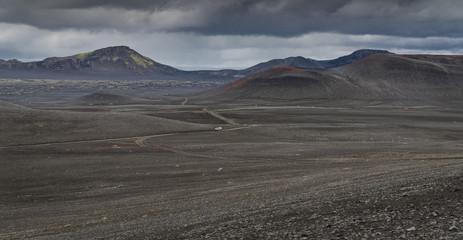 Landmannalaugar - vulkanische Landschaft mit bunten vulkanischen Bergen und einer Strasse auf der ein einzelner Geländewagen fährt