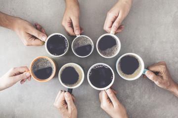 Ludzie ręce, trzymając filiżanki kawy