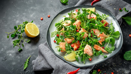 Fresh Salmon salad in asian style with sesame seeds, chili, lemon and green vegetables