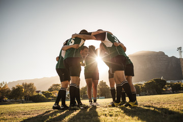 Rugby players huddling on sports field