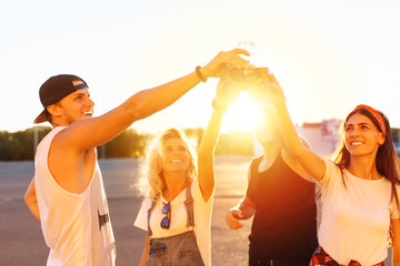 group of young people with glass bottles with a drink stand near the supermarket, on a yellow background, friends come off in full, cheerful mood, Sunny day, Lifestyl concept