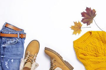Female orange knitted sweater, blue jeans, boots and autumn leaves on white background top view flat lay. Fashion Lady Clothes Set Trendy Cozy Knit Jumper Autumn accessories Female fashion look
