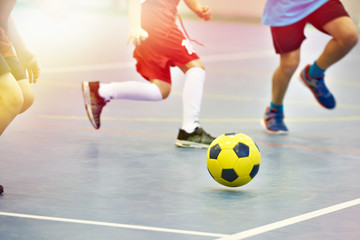 Children playing soccer indoors