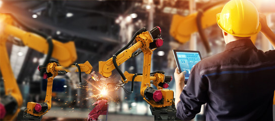 Engineer check and control welding robotics automatic arms machine in intelligent factory automotive industrial with monitoring system software. Digital manufacturing operation. Industry 4.0