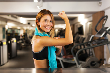 happy girl showing muscles in a fitness club