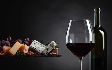 Glass of red wine with various cheeses , grapes and walnuts .
