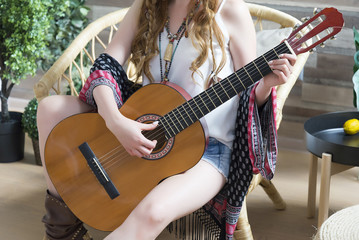 Female ore holds a seven-string classical guitar.