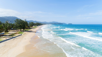 Beautiful wave crashing on sandy shore at karon beach in phuket thailand,aerial view drone shot.