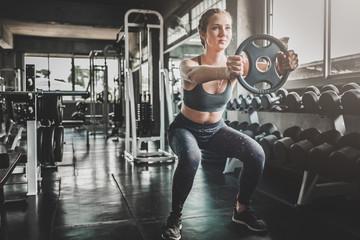 kobieta robi treningu z obciążnikiem na siłowni