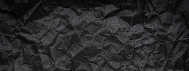 Ragged crumpled dark black paper texture background